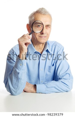 Old man looking through magnifying glass. Focus on magnyfiying glass. - stock photo