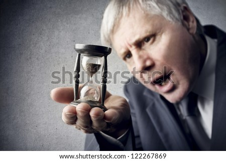 Old man looks at the sand in an hourglass - stock photo