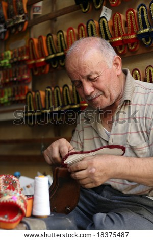 old man making colorful slippers for women
