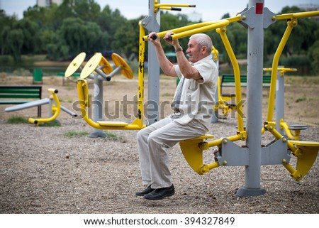 Old man making exercises on outdoor gym against green summer park as a background.