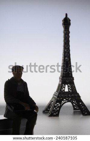 Old man miniature with a cap in front of eiffel tower in France - stock photo