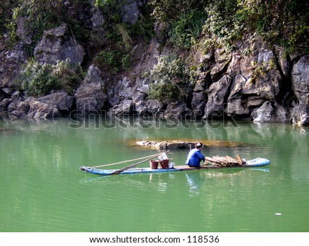 old man on small raft in China - stock photo