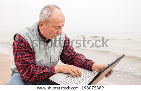 Old man on the beach with a laptop on a foggy day - stock photo