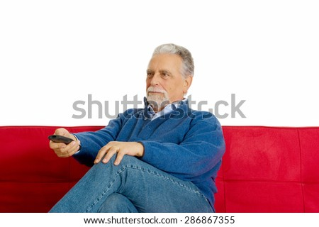 old man on the sofa with television remote control - stock photo