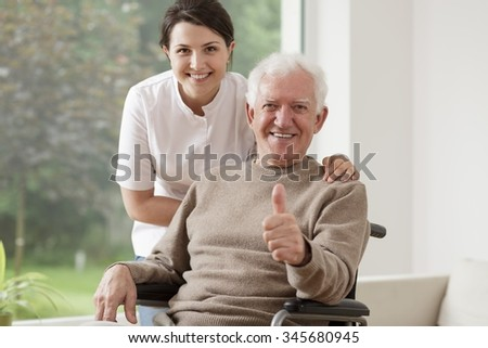 Old man on wheelchair holding thumb up - stock photo