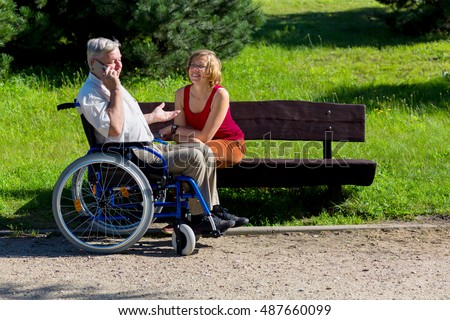 old man on wheelchair talking to the phone and young woman sitting on a bench