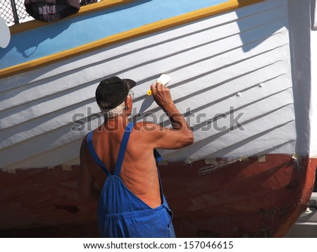 old man painting wooden fishing boat            - stock photo