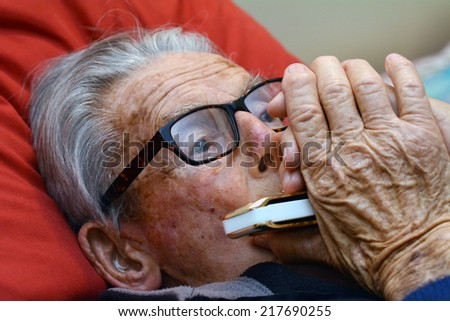 Old man play harmonica in bed. Concept photo of old age, lonely, alone, retirement, music, sad.