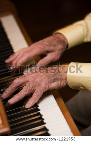 Old man plays piano so fast his fingers are blurred. - stock photo