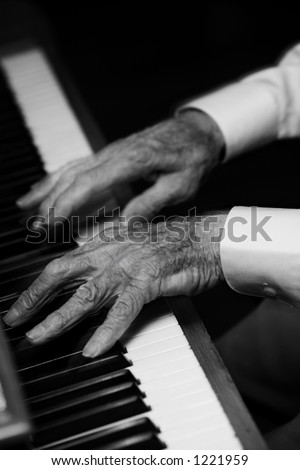 Old man plays piano with withered hands. Hands in motion leave motion trail as he plays quickly. - stock photo