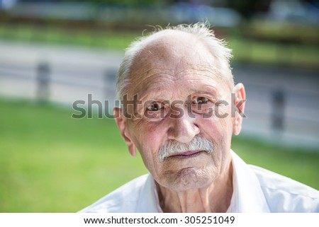 old man portrait in a park  - stock photo