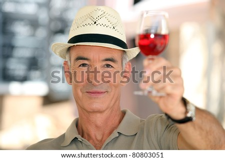 old man raising a glass of claret - stock photo