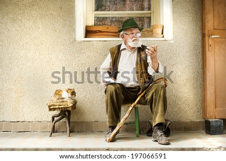 Old man reading the newspaper in front of his house - stock photo