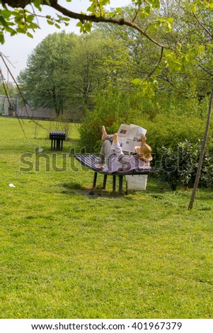 old man reading the newspaper in the park - stock photo