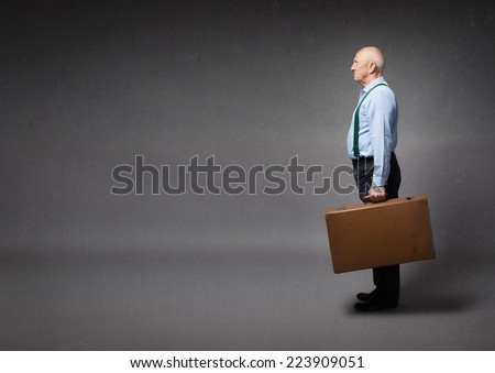 old man ready to leave with suitcase on hand - stock photo