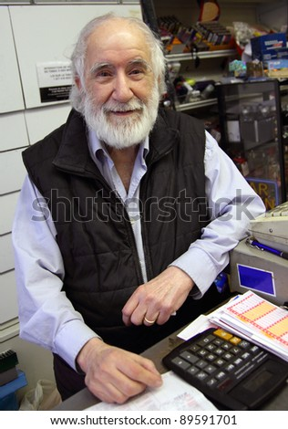 old man recieving people in his small store - stock photo