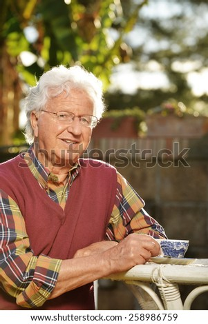 Old man relaxing in the garden at sunset - stock photo
