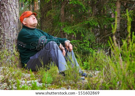 Old man resting in a forest near a tree
