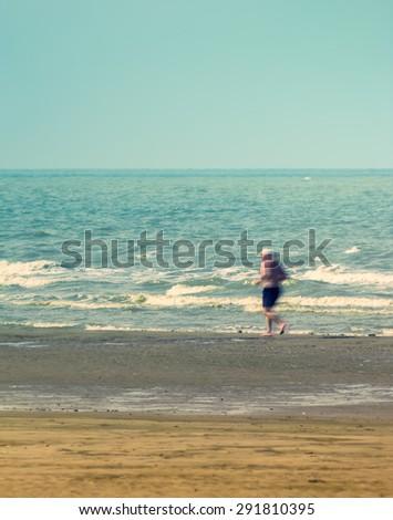 Old man running on beach, motion blur - stock photo