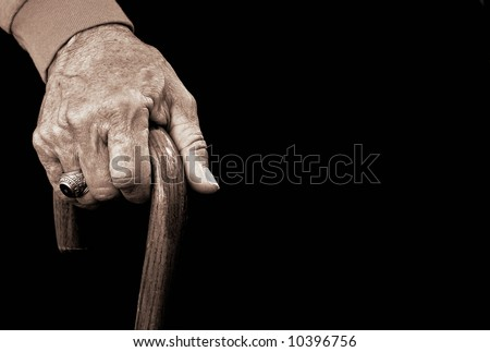 old man's hand with a walking cane - stock photo