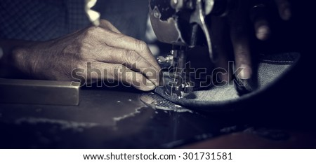 Old man's hands behind his sewing (vintage style)