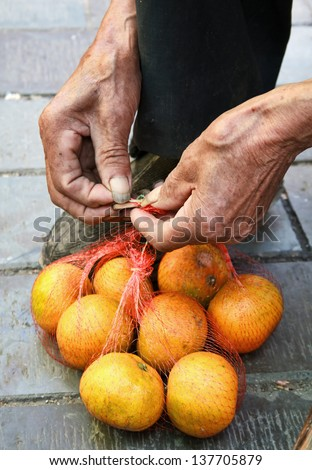 Old man's hands to tie a string bag of oranges for sale. - stock photo