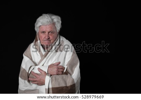 Old man sad wrapped in blanket on dark background with blank copy space for text message or slogan