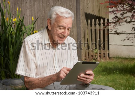 Old man senior citizen using tablet computer - stock photo