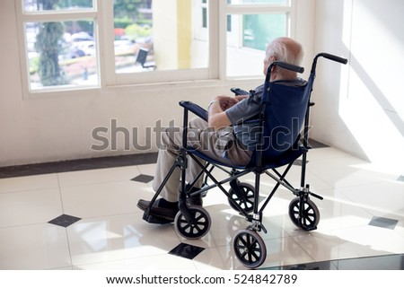 old man sit on wheelchair looking out to from the room fill lonely waiting for take care white room dementia and alzheimer