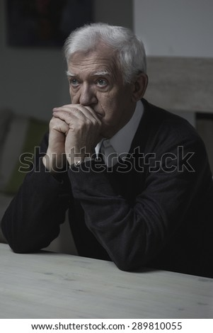Old man sitting at the table and praying - stock photo
