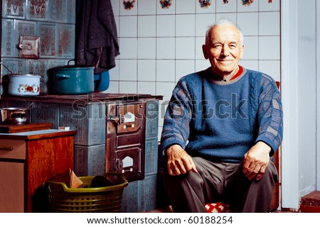 Old man sitting by his tile stove - stock photo