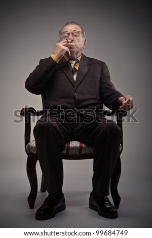 Old man sitting in a chair and smoking a cigarette - stock photo