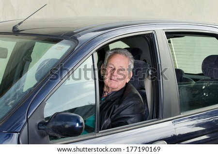 Old man sitting in car and looking in camera through opened window - stock photo