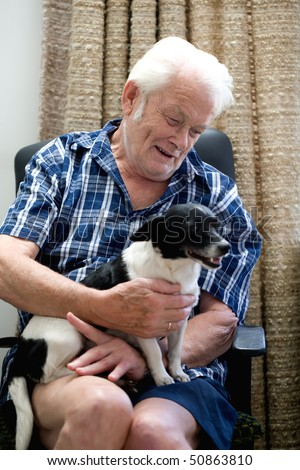Old man sitting on a chair playing with his dog, looking very happy. - stock photo