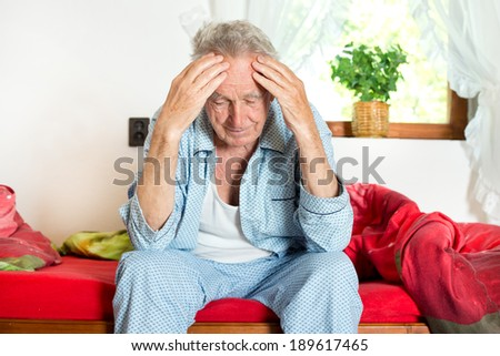 Old man sitting on bed and holding head with hands - stock photo