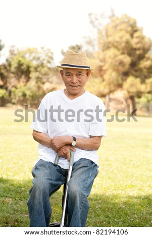old man sitting on chair  with walking stick in a park