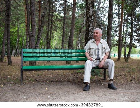 Old man sitting on the bench in park against trees as a background.