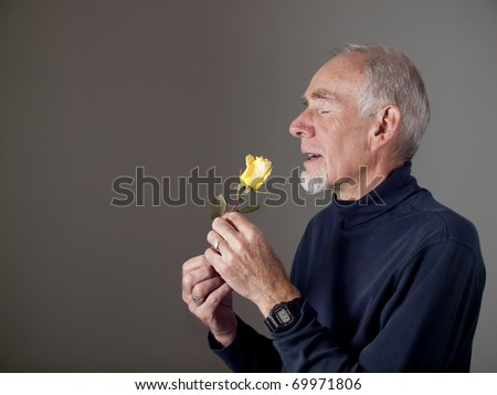 Old man smelling a rose - stock photo