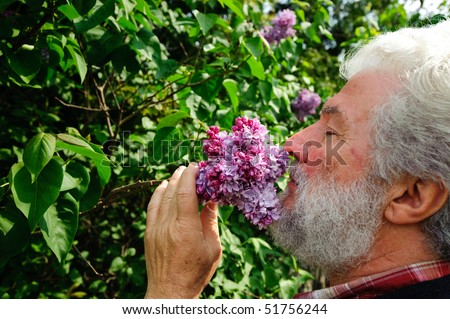 Old man smelling flowers - stock photo