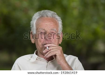 Old man smoking cigarette and enjoying life - stock photo