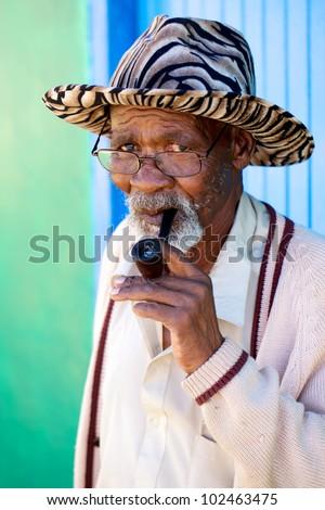 Old man smoking his pipe - stock photo