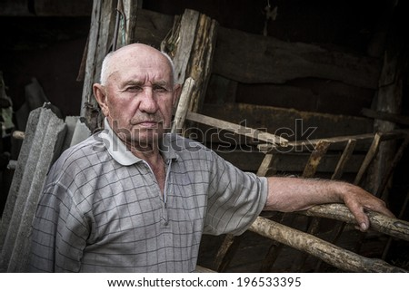 old man standing near the fence - stock photo