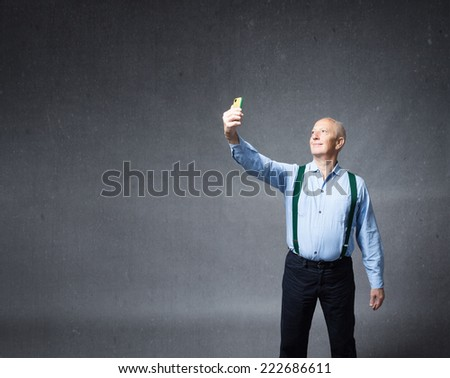 old man taking selfie with phone - stock photo
