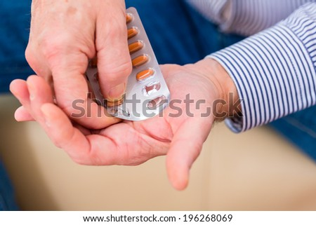 Old man taking too much medicaments at home - stock photo