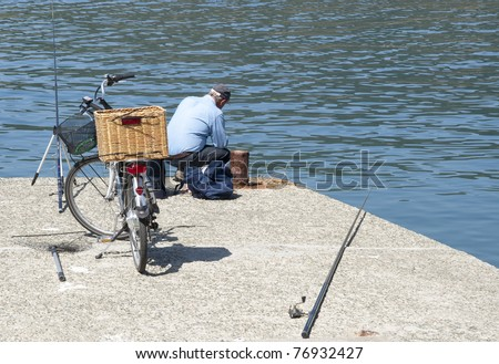 old man to fish, with a bicycle with a basket - stock photo