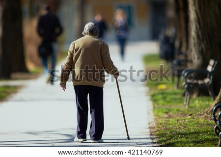Old man walking down the street with walking stick - stock photo