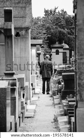 Old man walking in Montparnasse Cemetery in Paris (France). Rear view. Selective focus on the tombs and trees at the backgrounds. Aged photo. Black and white. - stock photo