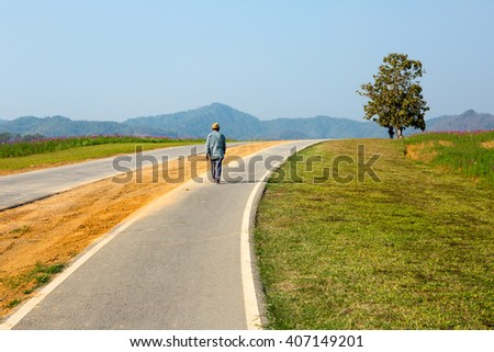 old man walking on a road  - stock photo