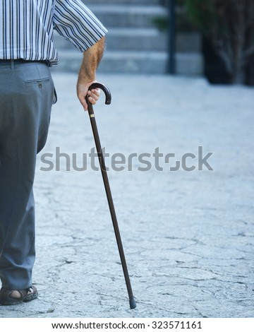 Old man walking with his hands on a wooden walking stick - stock photo