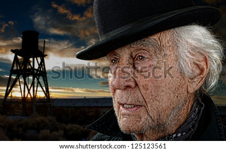 Old man wearing a black bowler hat with an old building and water tower against a dramatic sunset. - stock photo